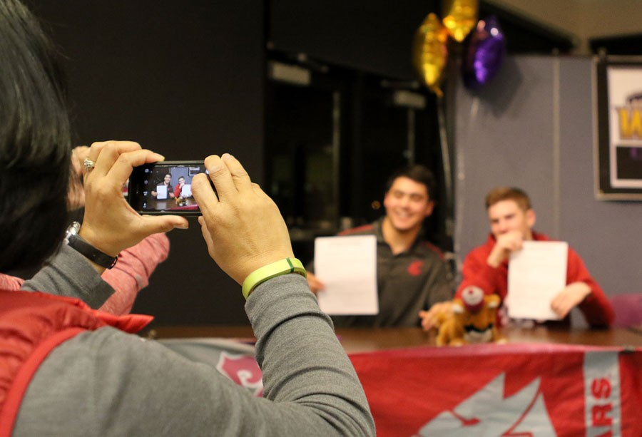 Wenatchee High School GEAR UP staffer Angela Prater photographs her son, senior Jacob Prater, and senior Cole Christman. Both are committed to play at Washington State University next year.