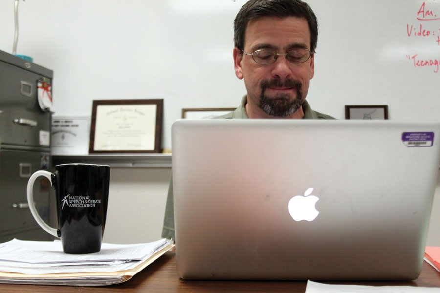 Debate+coach+and+English+teacher+Dave+Carlson+works+behind+his+computer+%E2%80%94+a+coffee+cup+only+a+reach+away+%E2%80%94+during+a+recent+class.
