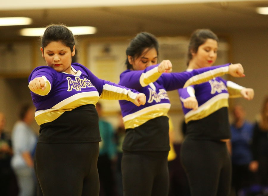 Three members of the Wenatchee High School varsity Apple-Ettes team perform at a pep assembly in the gym.