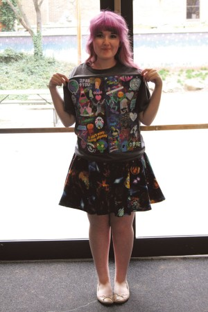 "Senior Mariah Hetterle displays shirts and a space patterned dress that she made. ""When I finish an outfit, I feel pretty cool. Like 'I just made this with my own hands!' It's a special feeling."""