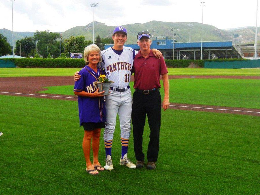 Senior Michael Buehn stands with his parents after a game.