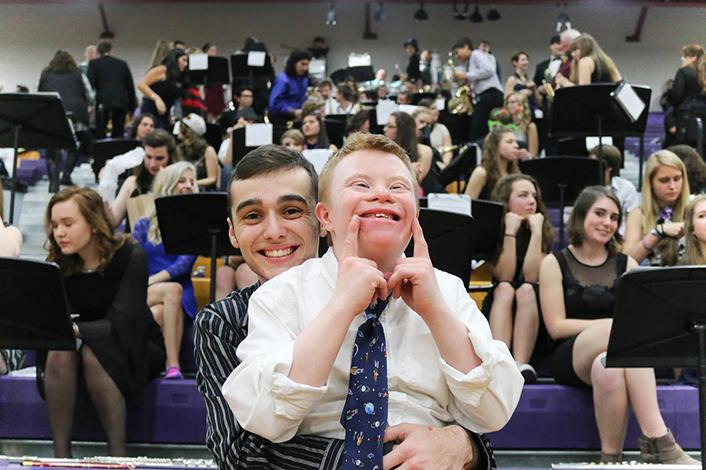 Sophomore Mason McRae smiles from ear to ear with former drum major Kevin Wilson while sitting in front of his bandmates. (Photo provided by Kendal Buak).